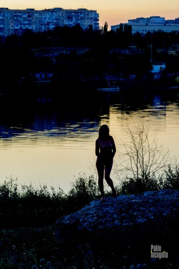 Silhouette of a naked girl on the lake at sunset. Nude photo by Pablo Incognito