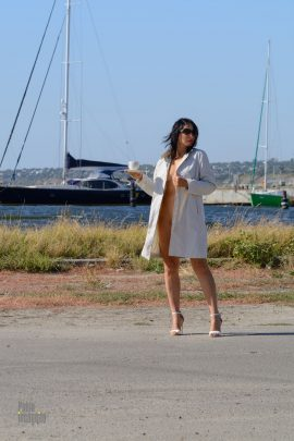 Girl in a raincoat on a naked body on the background of the yacht. Nude photo by Pablo Incognito