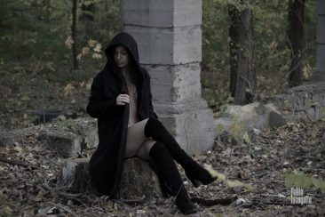 Naked girl in a coat with a hood sits posing in an autumn park. Nude photo by Pablo Incognito