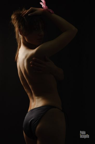 Girl posing nude, naked back on a black background. Nude photo by Pablo Incognito