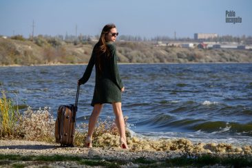 A girl with a suitcase on the river bank is going to pose for a nude photographer Pablo Incognito