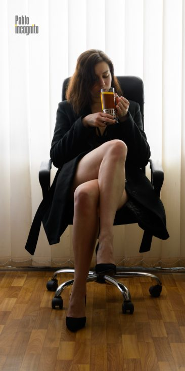 A naked girl in a coat sits in an armchair and drinks tea. Nude photo by Pablo Incognito