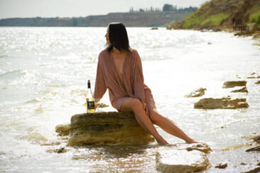 Girl on a stone by the sea with a glass of wine. Nude photo by Pablo Incognito