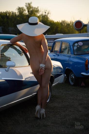 Обнаженная девушка в шляпе позирует возле ретроавтомобиля. Фото Пабло Инкогнито.