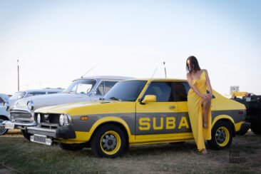 A girl in a long yellow dress poses near a yellow car. Nude photo session by Pablo Incognito