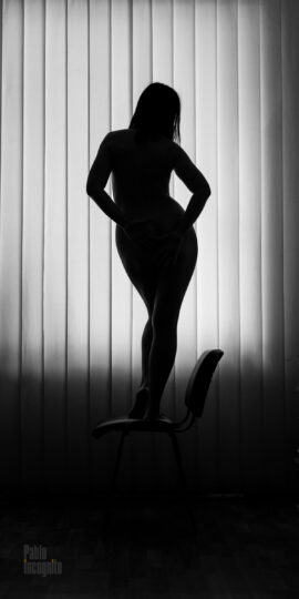 Silhouette of a naked girl on the background of the window. Pablo Incognito