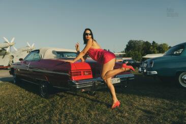 A girl in a crimson dress poses near a crimson Chevrolet Impala. Nude photo by Pablo Incognito