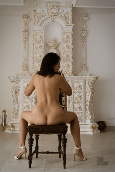 Nude woman sitting on a chair in a white hall. NUDE photo shoot by Pablo Incognito