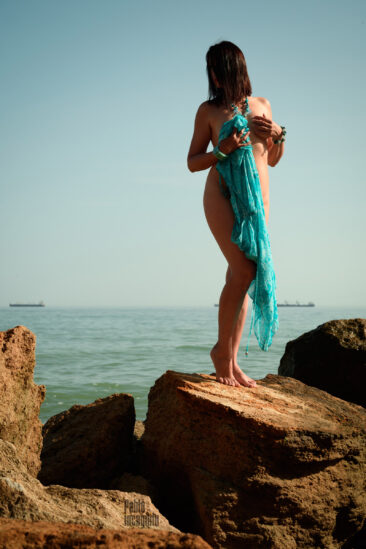 Nude girl with a turquoise cape on the stone. Nude photographer Pablo Incognito