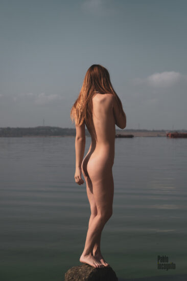 Young naked girl on a stone by the river. Nude photo by Pablo Incognito