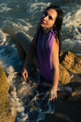Wet girl in a lilac cape posing nude on the beach. Photo by Pablo Incognito