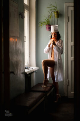 Dr. Iren lit a cigarette by the window in the hallway. Nude photo by Pablo Incognito