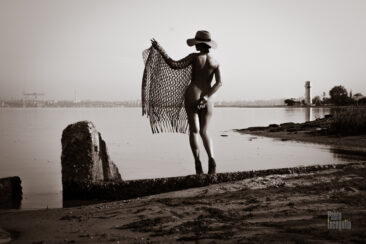 Nude in a net and a hat on the bank of the river. Nude photo by Pablo Incognito